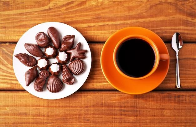 나무 테이블에 숟가락과 초콜릿 사탕을 넣은 커피 한 잔. 탑 뷰 포인트.