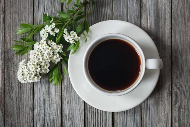Чашка кофе с весенними цветами на деревянном столе, выстрел под высоким углом