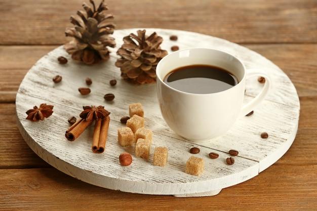 Чашка кофе с сахаром и корицей на белом деревянном коврике