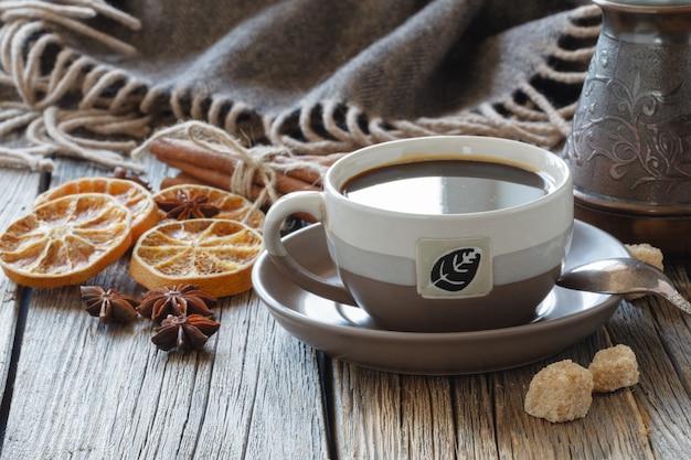 砂糖とスパイスの入ったコーヒーカップと木の板にコーヒーの穀物と木製の箱