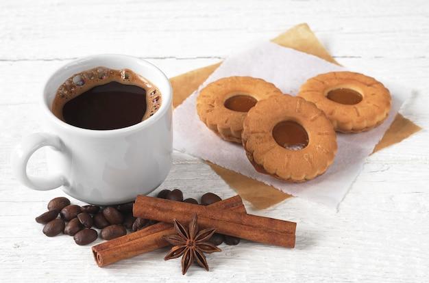 白い木製のテーブルにおいしいクッキーとコーヒーのカップ