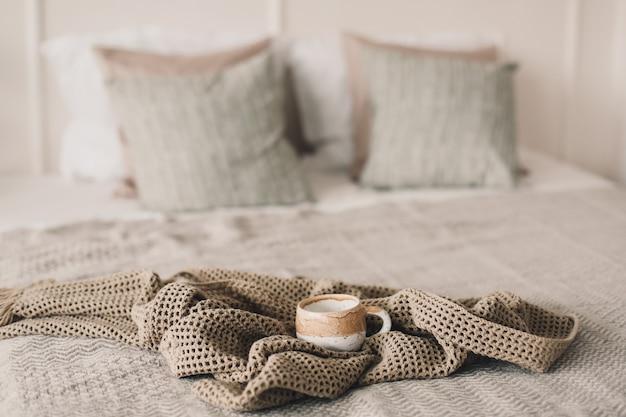 Чашка кофе с теплым пледом в постели Premium Фотографии