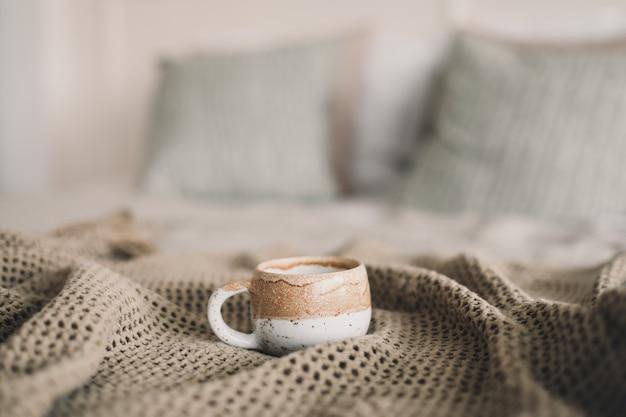 ベッドに暖かい格子縞のコーヒーのカップ