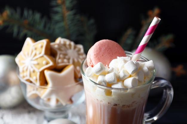 黒の背景にホイップクリームとお菓子とコーヒーのカップ
