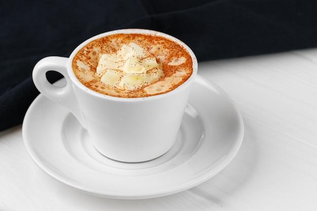 白いテーブルの上のホイップクリームとコーヒーのカップをクローズアップ