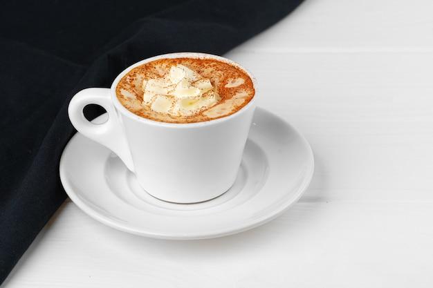 흰색 테이블에 휘 핑된 크림과 함께 커피 한잔