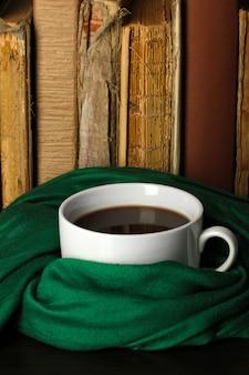 本の背景にスカーフで包まれたコーヒーのカップ