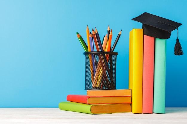 Чашка цветных карандашей и стопка книг на столе