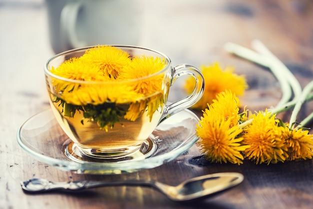 Чашка чая из одуванчика на деревенском деревянном столе.
