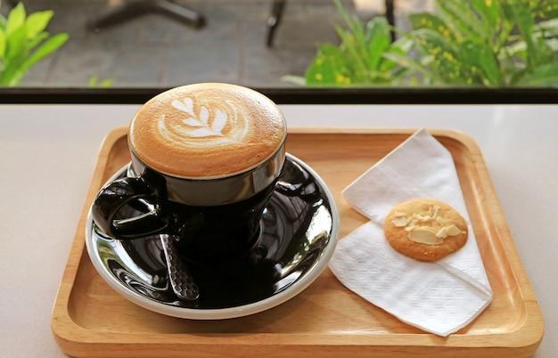 窓際のテーブルにバタークッキーとおいしいカプチーノコーヒーのカップ