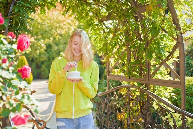 喜びのカップ。快楽主義とグルメ。咲き誇る庭でクリーミーなカプチーノをお楽しみください。女の子はグルメカプチーノを飲みます。女性は一人でカプチーノの神聖な味を楽しんでいます。コーヒー愛好家。純粋な楽しみ。