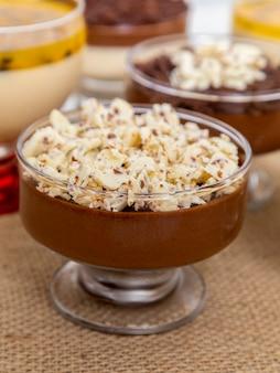 ミルクチョコレートムースとホワイトチョコレートの削りくず、ガナッシュムース、パッションフルーツムースのデザートカップ。