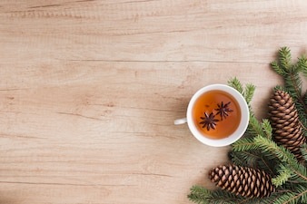 Cup of drink near coniferous twigs and snags