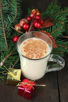 나무 배경에 전나무 가지와 크리스마스 장식이 있는 에그노그 컵