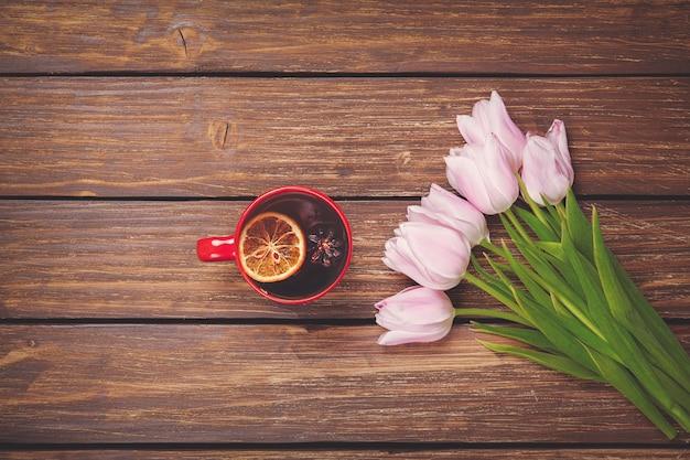 木の春のチューリップとイングリッシュティーのカップ