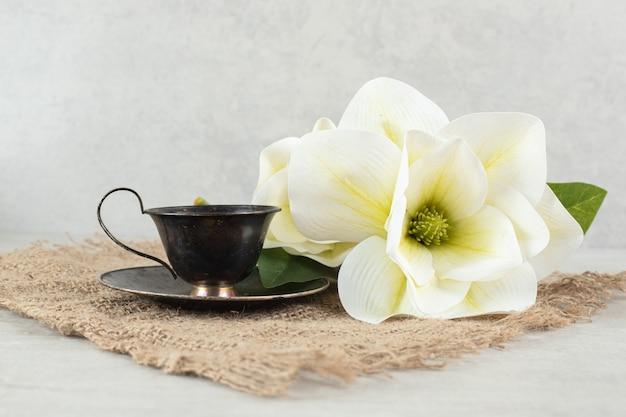 Чашка эспрессо и белые цветы на мешковине