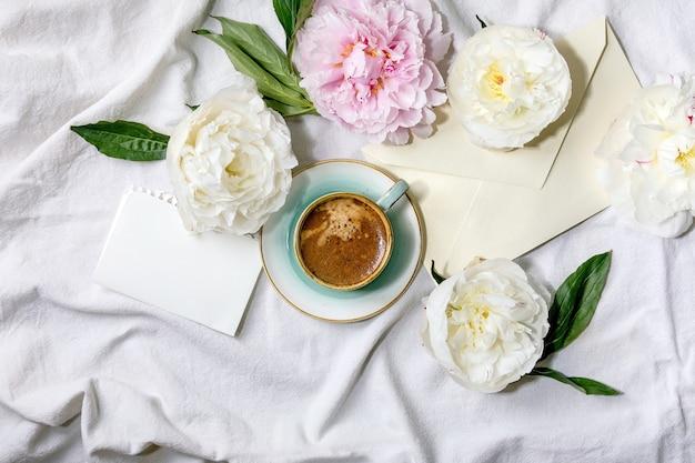 Чашка кофе эспрессо, чистый лист бумаги, конверт, цветы розовых и белых пионов с листьями на белой хлопковой текстильной поверхности