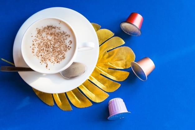 에스프레소 커피 한 잔, 포드 및 캡슐과 함께 제공되는 카푸치노. 다채로운 커피 캡슐입니다.