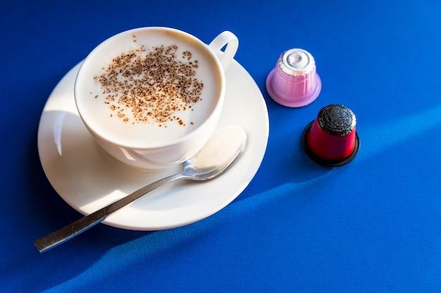 에스프레소 커피 한 잔, 카푸치노는 파란색 테이블에 캡슐과 꼬투리와 함께 제공됩니다.커피 머신, 다채로운 커피 캡슐. 좋은 아침 따뜻한 음료. 복사 공간