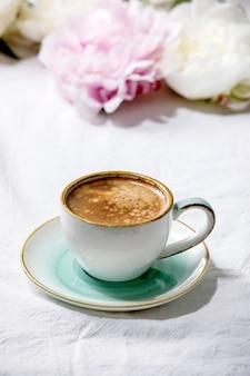 Чашка кофе эспрессо, цветы розовых и белых пионов с листьями на белой хлопковой текстильной поверхности