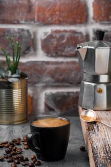 Чашка кофе эспрессо, над кружкой поднимается пар, кофейник и кофейные зерна на сером каменном столе, кирпичная кладка. крупный план, перерыв на кофе или завтрак, время кофе