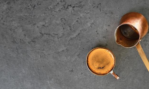 Чашка кофе эспрессо с ароматной пеной на каменном кухонном столе, рядом с туркой. вид сверху с копией пространства для вашего текста