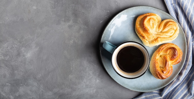 Чашка кофе эспрессо с двумя сладкими булочками в форме сердца в тарелке на сером бетоне.