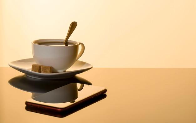 白いカップでエスプレッソのカップと反射とガラステーブルの上のスマートフォン