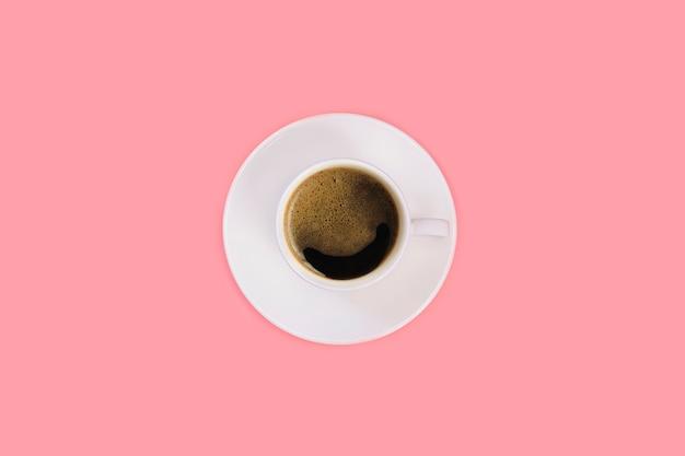 Чашка эспрессо на белом блюдце на розовом фоне. вид сверху, плоская планировка, копия пространства