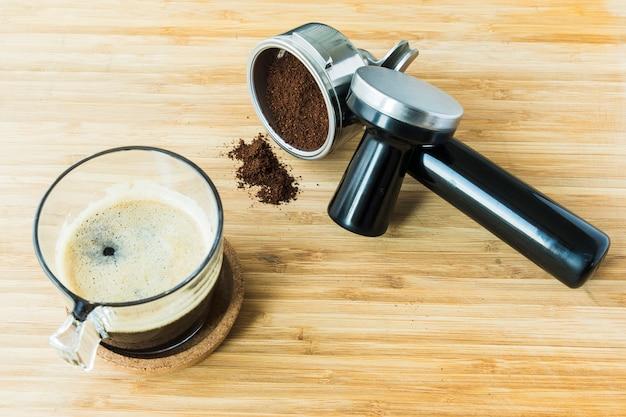エスプレッソのカップ、挽いたコーヒーの木製ボード