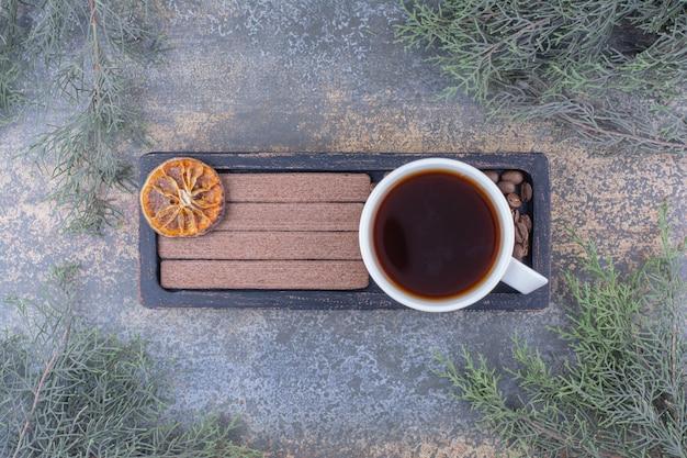 Чашка эспрессо, печенье и кофейные зерна на черной тарелке. фото высокого качества
