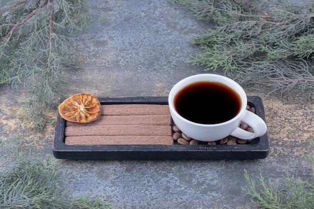 黒いプレートにエスプレッソ、スティックビスケット、コーヒー豆のカップ。