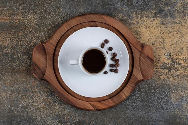 Чашка эспрессо с кофейными зернами на деревянной доске.