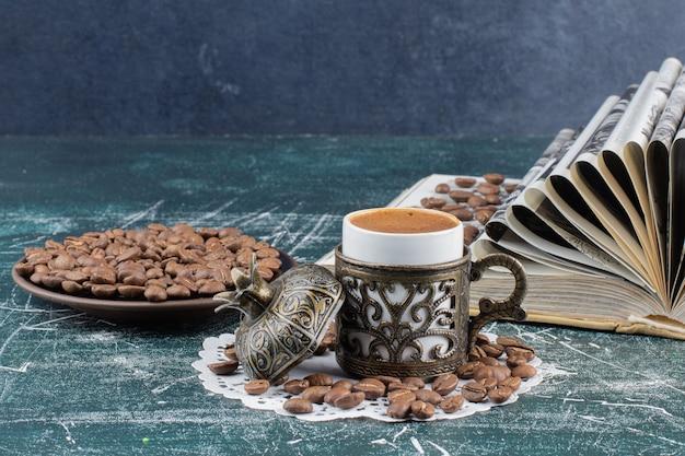泡立つコーヒーのカップ、コーヒー豆のプレート、大理石のテーブルの本。