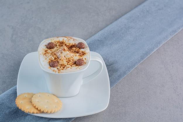 石の上の泡立ったホットコーヒーとビスケットのカップ。