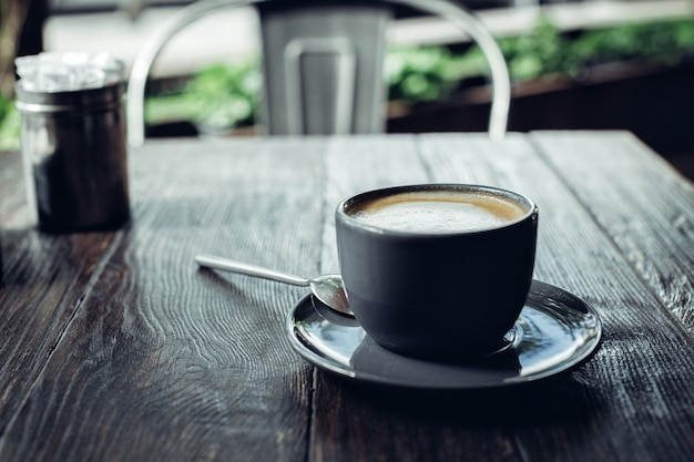 暗い木製のテーブルの上の泡と香りのよいコーヒーのカップ