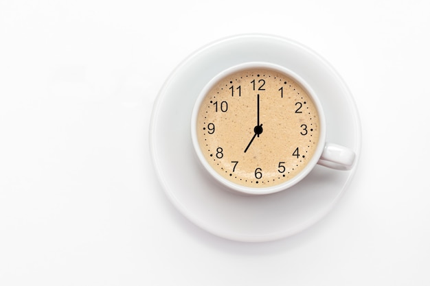 Чашка свежего капучино со знаком часов. вид сверху на белом фоне