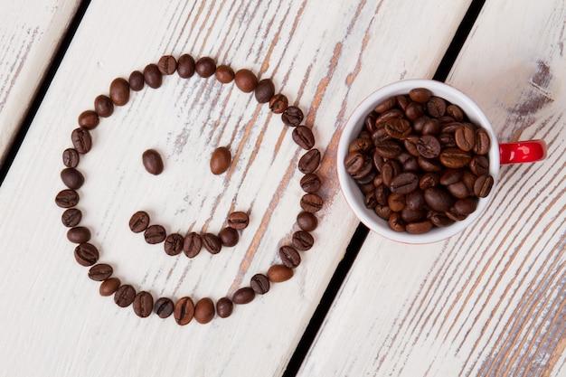 신선한 커피 원두와 웃는 얼굴의 컵. backgound에 흰색 나무 널빤지입니다.