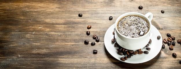 木製のテーブルの上の淹れたてのコーヒーのカップ