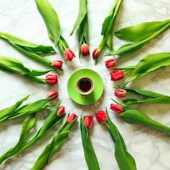 Чашка свежего кофе с красными тюльпанами на мраморном макете