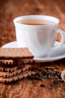 Чашка свежего травяного чая и печенья крупным планом на деревянный стол