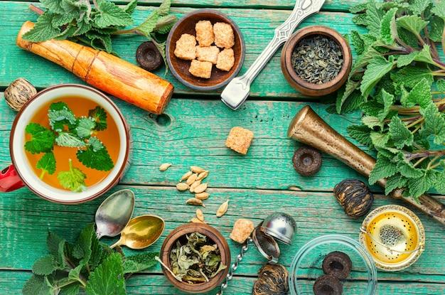 Чашка свежего травяного чая с мелиссой на деревянном столе. ингредиенты травяного чая