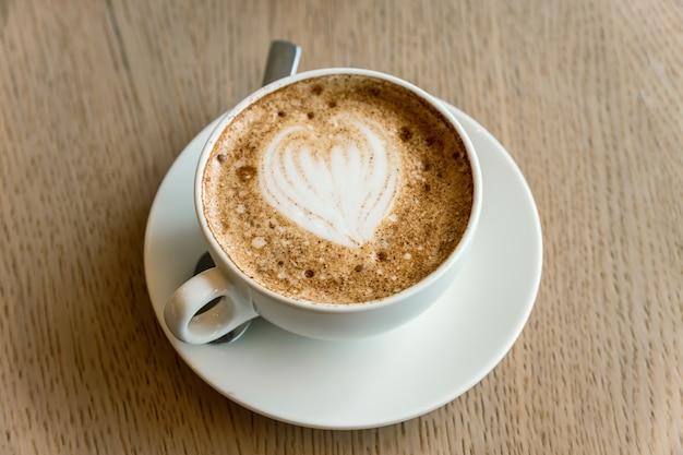Чашка свежезаваренного капучино с пеной латте-арт на столе в кафетерии.