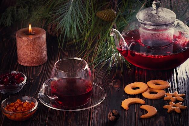 淹れたてのフルーツとベリーの赤茶、ダークムーディー、茶道のカップ。モミの枝。キャンドルとテーブルの上のクッキー。
