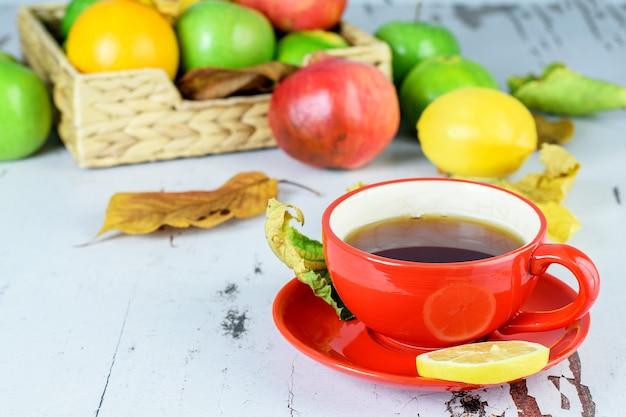 Чашка фруктового чая с лимоном. тропические цитрусовые на белом деревенском столе.