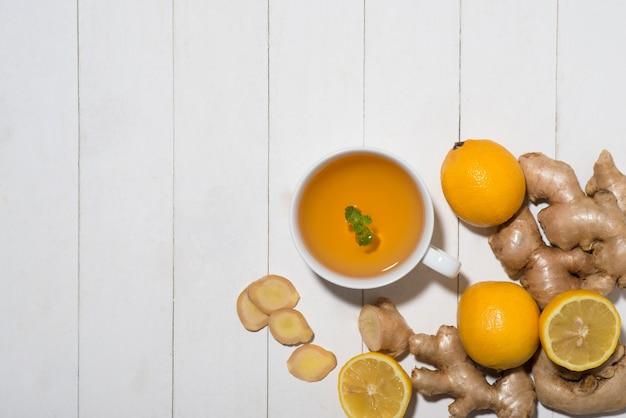 흰색 나무 바탕에 레몬과 꿀을 넣은 생강차 한잔.