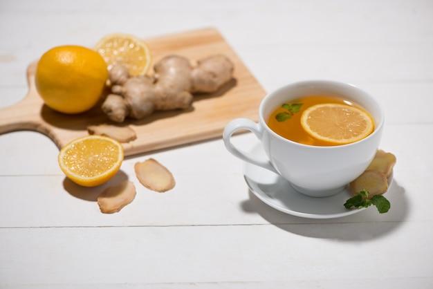 Чашка имбирного чая с лимоном и медом на белом деревянном фоне.