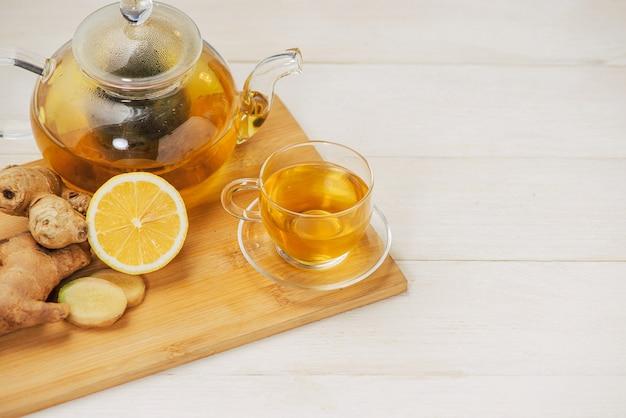 흰색 나무 바탕에 레몬과 꿀을 넣은 생강차 한 잔.
