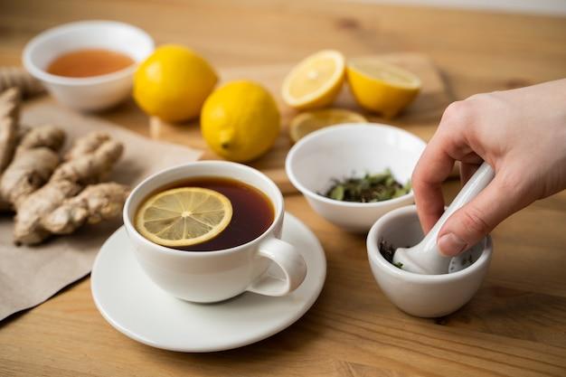 Чашка имбирного чая с лимоном на деревянном столе.