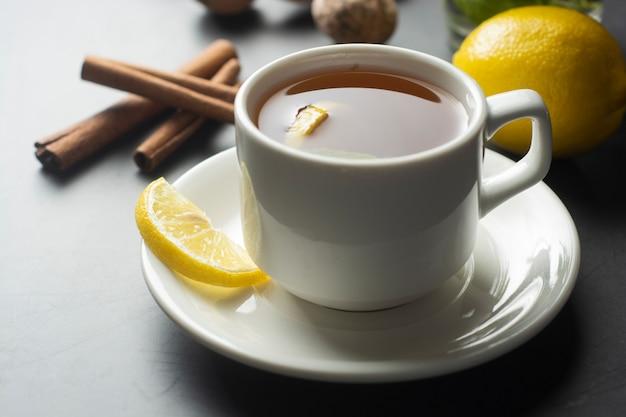 Чашка имбирного чая с лимонами и листьями мяты на темной поверхности,
